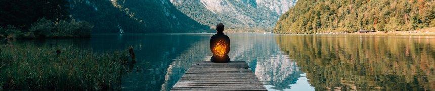 Tummo. Mann sitzt auf dem Steg am See und meditiert. Eine Feuerkugel breitet sich über seinen Körper aus.